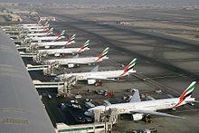 Вид на взлетно-посадочную полосу аэропорта, здание аэровокзала и припаркованные рядом с ним несколько авиалайнеров.