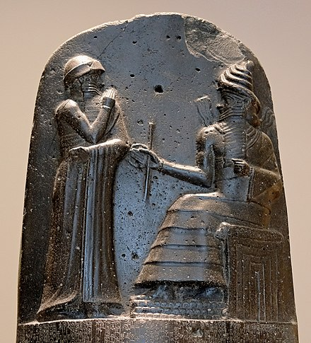 Hammurabi (standing), depicted as receiving his royal insignia from Shamash (or possibly Marduk). Hammurabi holds his hands over his mouth as a sign of prayer (relief on the upper part of the stele of Hammurabi's code of laws). F0182 Louvre Code Hammourabi Bas-relief Sb8 rwk.jpg