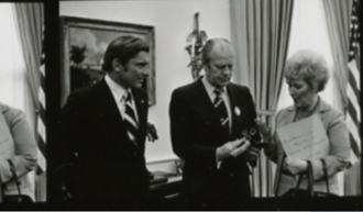 Mary Brooks - Mint Director Mary Brooks presents President Gerald Ford (center) with the first set of the Bicentennial coins, November 13, 1974 as American Revolutionary Bicentennial Administration Director John Warner looks on.