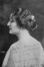 Head and shoulders rear-view studio portrait of an elegant lady in her thirties looking to her left. She is wearing a simple dress but has an elaborate hair-style with jewellery. The portrait has been partially over-written with a greeting and signature by the sitter.