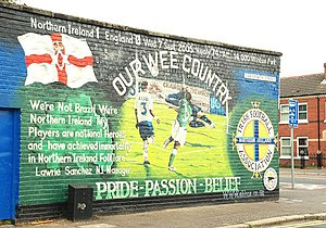 "A large mural on a wall. Prominent features include the Ulster Banner, the IFA logo, the scoreline ""Northern Ireland 1, England 0"", and the captions ""OUR WEE COUNTRY"" and ""PRIDE – PASSION – BELIEF"""