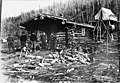 Four men and a woman standing in front of a log cabin with firewood in foreground and tent elevated on platform in back, Alaska (AL+CA 2536).jpg