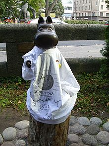 A dark metallic statue of a cartoon hippopotamus wearing a white t-shirt with the Wikipedia logo and signatures in various languages.