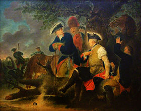 Four men are gathered under a tree. One, Frederick the Great, has his shirt sleeve rolled up and a second man is wrapping a bandage around his arm. A grenadier watches what he does. Another man, in a tri-cornered hat, stands at Fredrick's side. In the background, soldiers load and fire cannons.