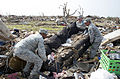 From left, U.S. Air Force Master Sgt. Dante Alexander, Tech. Sgt. Anthony Burch and Chief Master Sgt. Kevin Vegas, all assigned to Tinker Air Force Base, Okla., help clean up a damaged home in Moore, Okla 130524-F-IE715-327.jpg