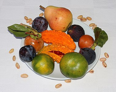 Fruit on a plate. Pear, figs, persimmons, bitter melon (momordica), plums and tangerines. Marmaris, Turkey