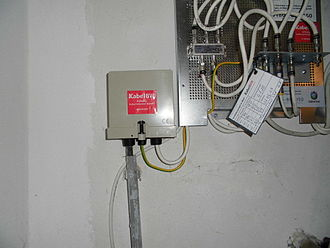 Cable television - A cable television distribution box (left) in the basement of a building in Germany, with a splitter (right) which supplies the signal to separate cables which go to different rooms