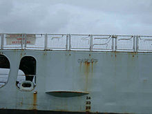 "Close-up of a ship's light blue hull with the word ""Cardiff"" embossed on to it. There is rust drizzling down from the lettering."