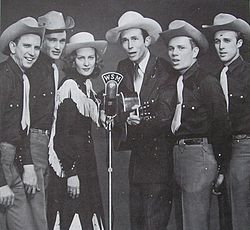A group of six men and one woman wearing cowboy hats, standing around a microphone. The man third from right is holding a guitar.