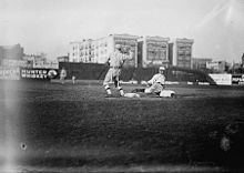 A black-and-white photograph of a baseball player sliding into a base