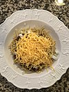 Spaghetti topped with chili, onions, and cheese