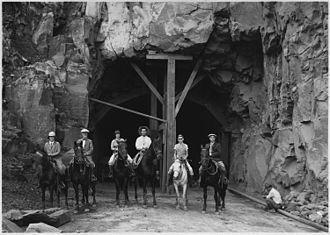 Zion – Mount Carmel Highway -  A horseback party at the western entrance to Zion Tunnel. The tunnel shortened the distance from Zion to Bryce by 70 miles. 1929