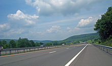 An expressway, photographed from its right shoulder, continuing north toward a green hillside in the center of the image, where it curves leftward. There is another hillside off to the left in the distance.