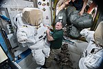 ISS-54 Scott Tingle works on a spacesuit inside the Quest airlock.jpg