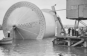 Operation Pluto - Laying the pipeline: a 'Conundrum' being moved into position into a specially constructed dock in preparation for the winding on of the pipe.