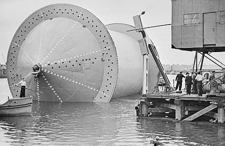 Laying the pipeline: a 'Conundrum' being moved into position into a specially constructed dock in preparation for the winding on of the pipe. IWM-T-30-Conundrum-preparation.jpg