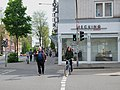 Ice cream eater and cyclist crossing the street in Aachen, DE (DSCF5905).jpg