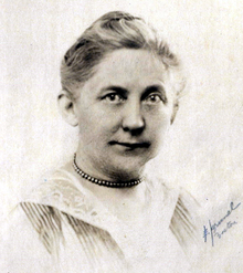 Middle-aged white woman wearing a necklace.