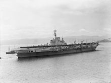 Black and white photograph showing a World War II-era aircraft carrier in a body of water which is surrounded by low hills. The bow of a smaller ship is visible behind the aircraft carrier.