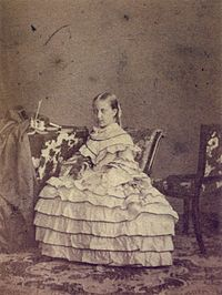 A photograph of a young, light-haired Isabel wearing an elaborate dress with a layered, hooped skirt and seated in front of a table that holds several books
