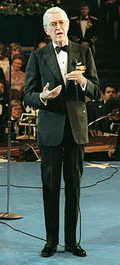 An elderly Stewart standing in a tuxedo on a stage, holding a microphone