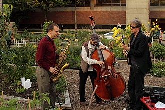 A jazz trio playing in a community garden. Jazz Trio in Community Garden (5045973149).jpg