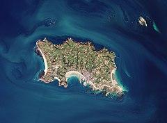 Zdjęcie satelitarne. Widać na nim wyspę Jersey z kosmosu. Na wyspie, na tym zdjęciu widoczne są pola, zabudowania oraz lasy, skaliste klify i plaże Jersey.