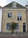 foto van Pand met gevel ontdaan van top en ontlastingsbogen met verdiepte boogvelden boven de vensters van de verdieping