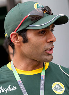 Photographie de profil, d'un homme de type indien, en gros plan, avec des vêtements vert foncé.