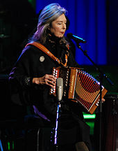 A woman in dark clothing behind a microphone stand on a stage; her eyes are closed, and she is playing an accordion