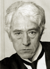 A white-haired man in his fifties, wearing a black jacket and tie and white shirt.
