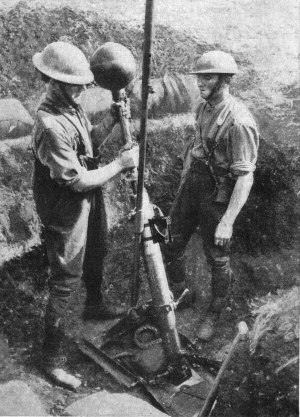 58th Divisional Trench Mortar Brigade - British troops loading a 'Toffee-Apple' bomb into a 2-inch trench mortar with attached periscope post. This appears to be a training exercise because no fuze is visible.