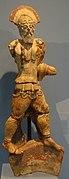 Statuette en terre cuite d'un soldat marchant et portant un casque à crête et une armure.