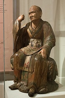 Monk with stern face and slight protrusion in skull, sitting and holding his hand as though he is holding a staff