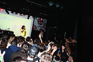 "Galang (song) - M.I.A performing ""Galang"" at the beginning of her Arular Tour in 2005, with the single artwork in the background"