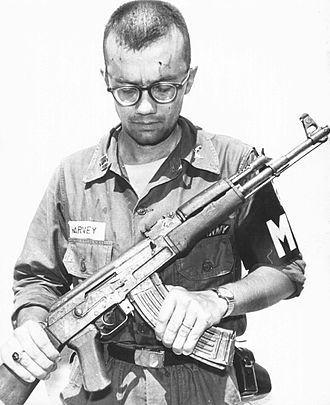 Military police - A US Army MP inspects a Soviet AK-47 recovered in Vietnam, 1968.