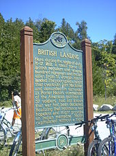 A historical plaque at British Landing, mounted atop wooden poles. Bikes are chained to the poles.