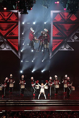 """Give Me All Your Luvin' - The performance of """"Give Me All Your Luvin"""" during The MDNA Tour, featuring Madonna dressed up in a majorette's costume and a drumline suspended in mid-air."""