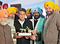 Manish Tewari being presented a memento by the officials of Grewal Sports Association, during the Kila Raipur Rural Sports festival, in District Ludhiana on February 02, 2014.jpg