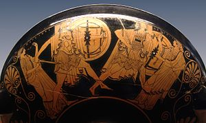 photographie d'une poterie grecque. Quatre personnages. Ménélas armé comme un hoplite poursuit Pâris qui s'enfuit et cherche protection aurpès de la déesse Aphrodite armée d'un arc