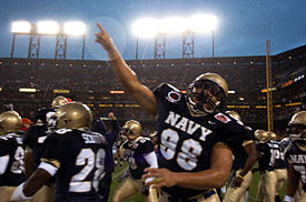 An American football player in uniform points to the sky in rainy conditions under stadium lights.