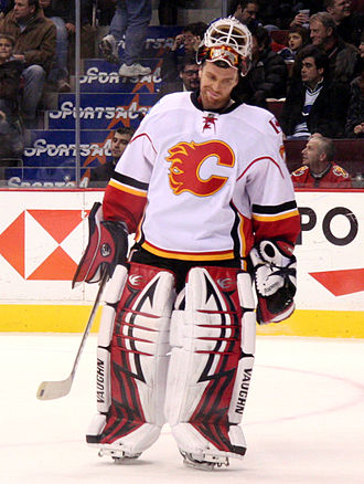 Miikka Kiprusoff -  alt = a hockey goaltender in a white jersey with a stylized red C logo on his chest and his mask raised above his forehead stares down at the ice as he is skating.