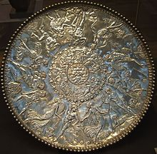 A large silver dish, decorated in bas relief in three rings. In the center ring, whose diameter is roughly 1/7 of the whole dish, is the face of a full-bearded man, with four bird heads pointing outwards along the diagonals. Around the second ring, frolicking sea creatures such as nereids are depicted; this ring's diameter is roughly 3/7 of the dish. Around the outermost ring, humans and a faun are depicted as dancing, making music, drinking and enjoying other pastimes.