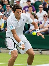 Raonic dressed in all white, bending forward slightly. His racquet is in his right hand, below the ball, about to make contact.