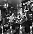 Mrs Pitt, wife of the landlord, pours a pint of beer for a naval officer in the saloon bar of 'The Cricketers' pub in Brighton during 1944. D22509.jpg