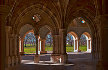 Multiple interior and exterior stone arches frame a view looking out from a chapter house, revealing a view of orchard trees beyond an expanse of bare ground.