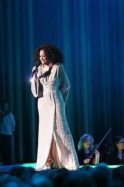 A woman in a long white coat singing into a microphone.