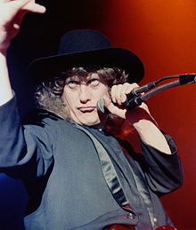 A man with curly hair holds a microphone to his face. He wears a black hat and jacket.