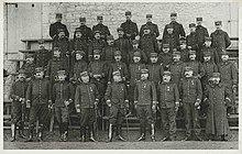 Fotografia a preto e branco, em que os oficiais, fardados, com quepe e espada, estão dispostos em quatro filas.