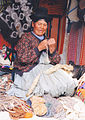 Old Indian female spinning on market Peru.jpg